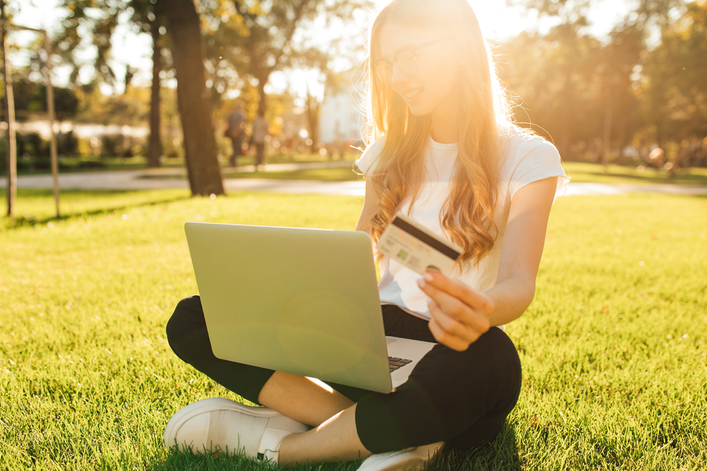 Woman sitting outside shopping online